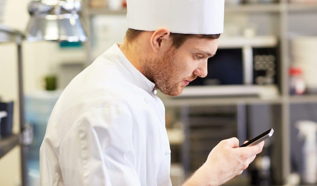 chef che utilizza lo smartphone nella cucina di un ristorante