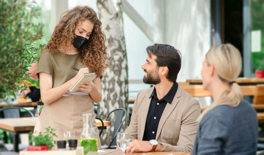 cameriera a commensali ordinano al ristorante seduti in un tavolo all'aperto