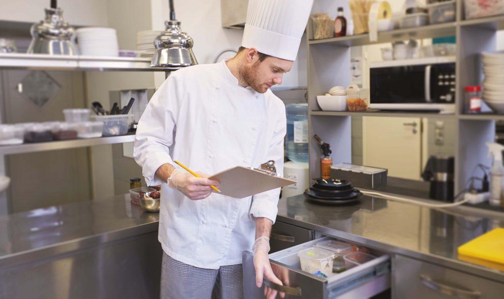 chef che controlla l'inventario in cucina controllando anche la conservazione dei diversi prodotti alimentari