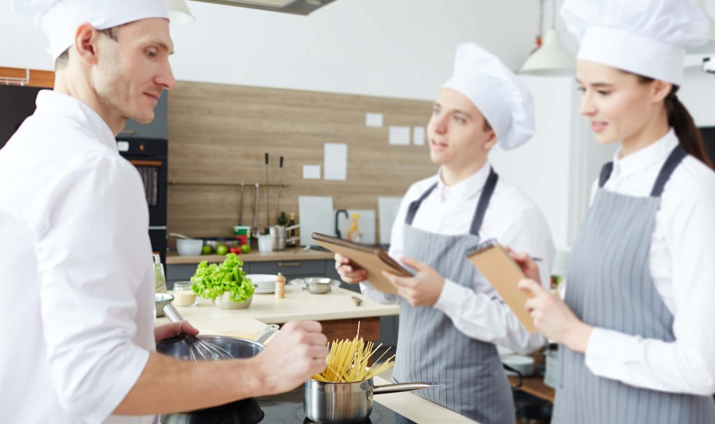 creazione del menù nella cucina del ristorante da parte dello chef e gli aiuto cuochi