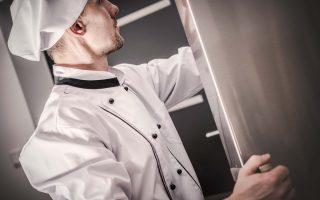 Chef che sceglie gli ingredienti presenti nel frigo della sua cucina