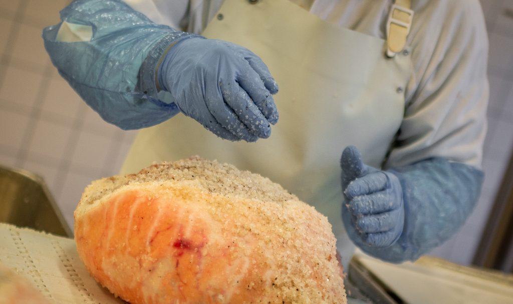 processo di salagione dei prosciutti svolto artigianalmente dall'addetto presso il salumificio wolf di sauris di sotto