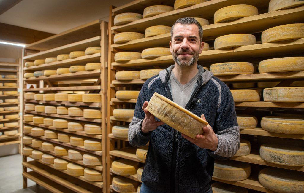 sebastiano il proprietario di malga alta carnia nella stanza di affinatura e stagionatura dei formaggi di malga