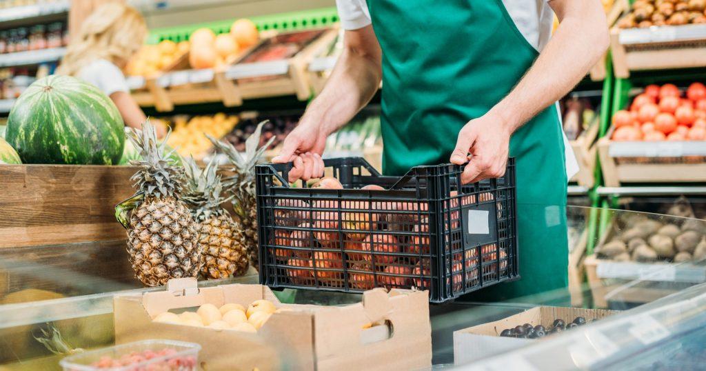 assistente alla vendita con cassetta di frutta in negozio di frutta e verdura