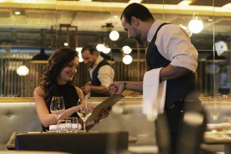 cameriere indica alla cliente le proposte relative al menu del ristorante